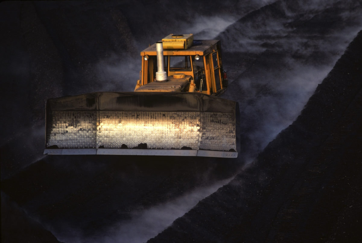 Moving coal with bulldozer for transport by train.