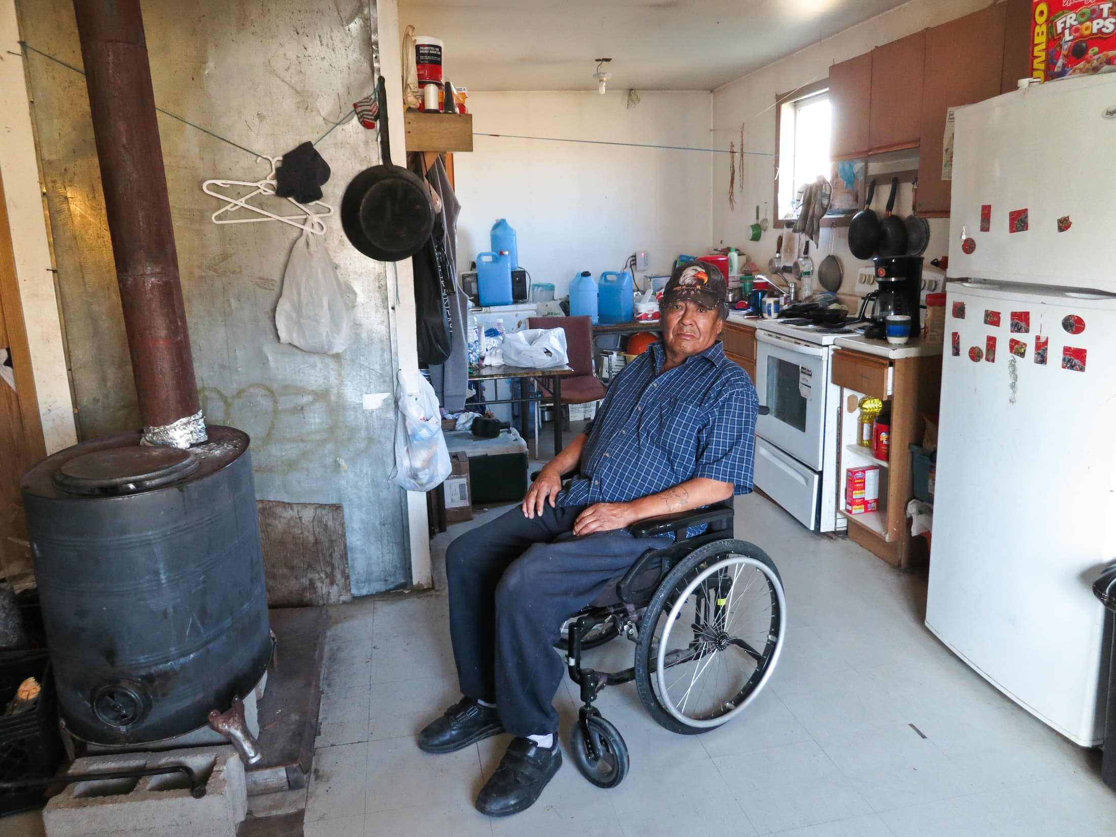 Walter Sakanee, an elder living in Neskantaga First Nation, has had difficulty fighting infections in his legs. He relies on his family members to collect safe drinking water for him in blue plastic jugs from a reverse osmosis machine located at the community's water treatment plant. He is not able to access the plant on his own due to his physical disability. Photo: Samer Muscati / Human Rights Watch