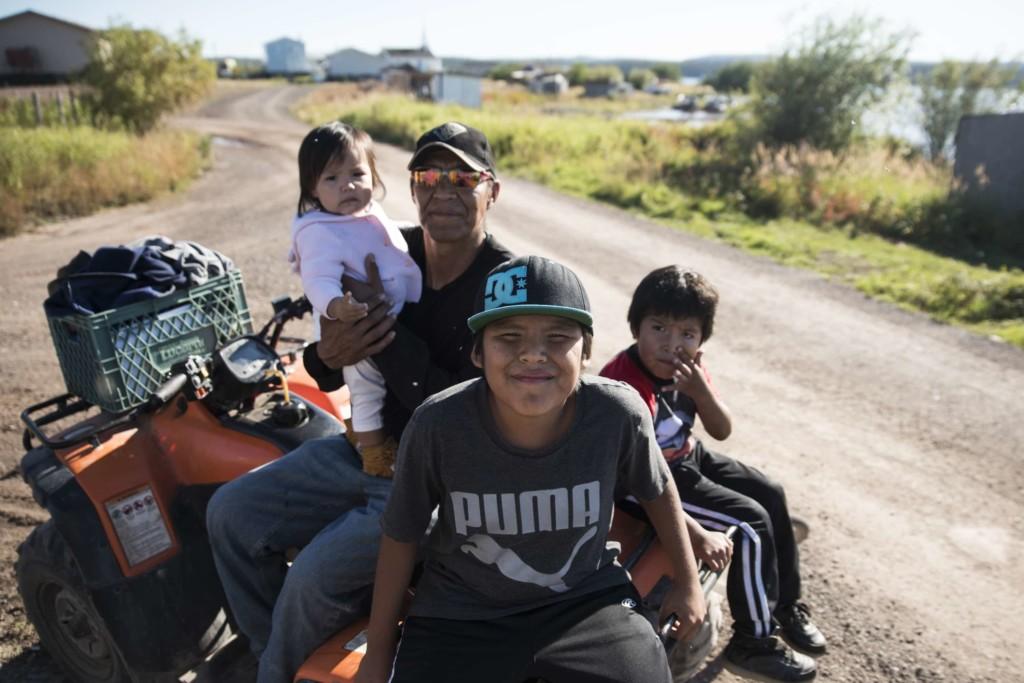 Derek Sanderson with children on a quad