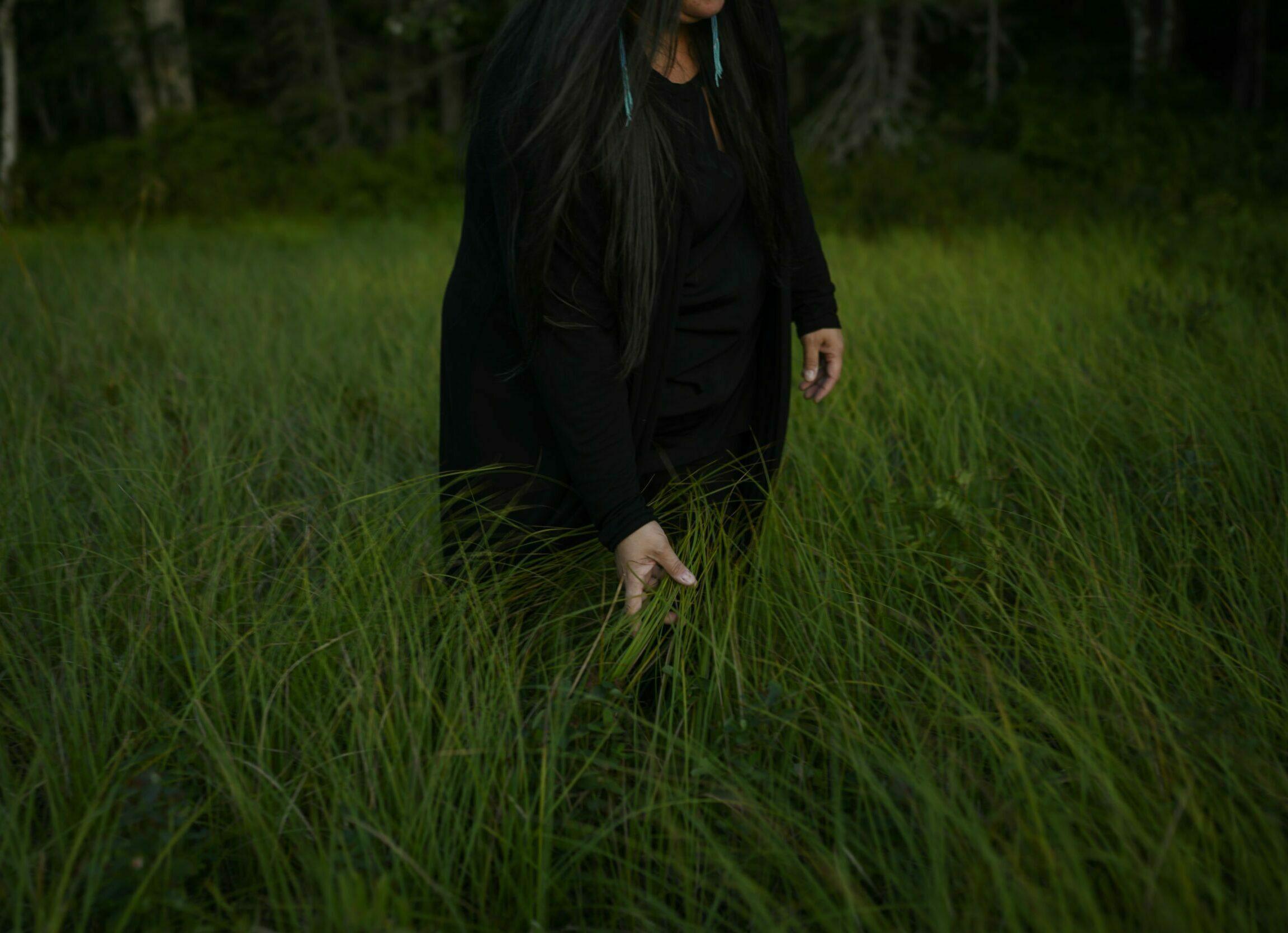 Melissa Labrador runs her hand through the tall grass