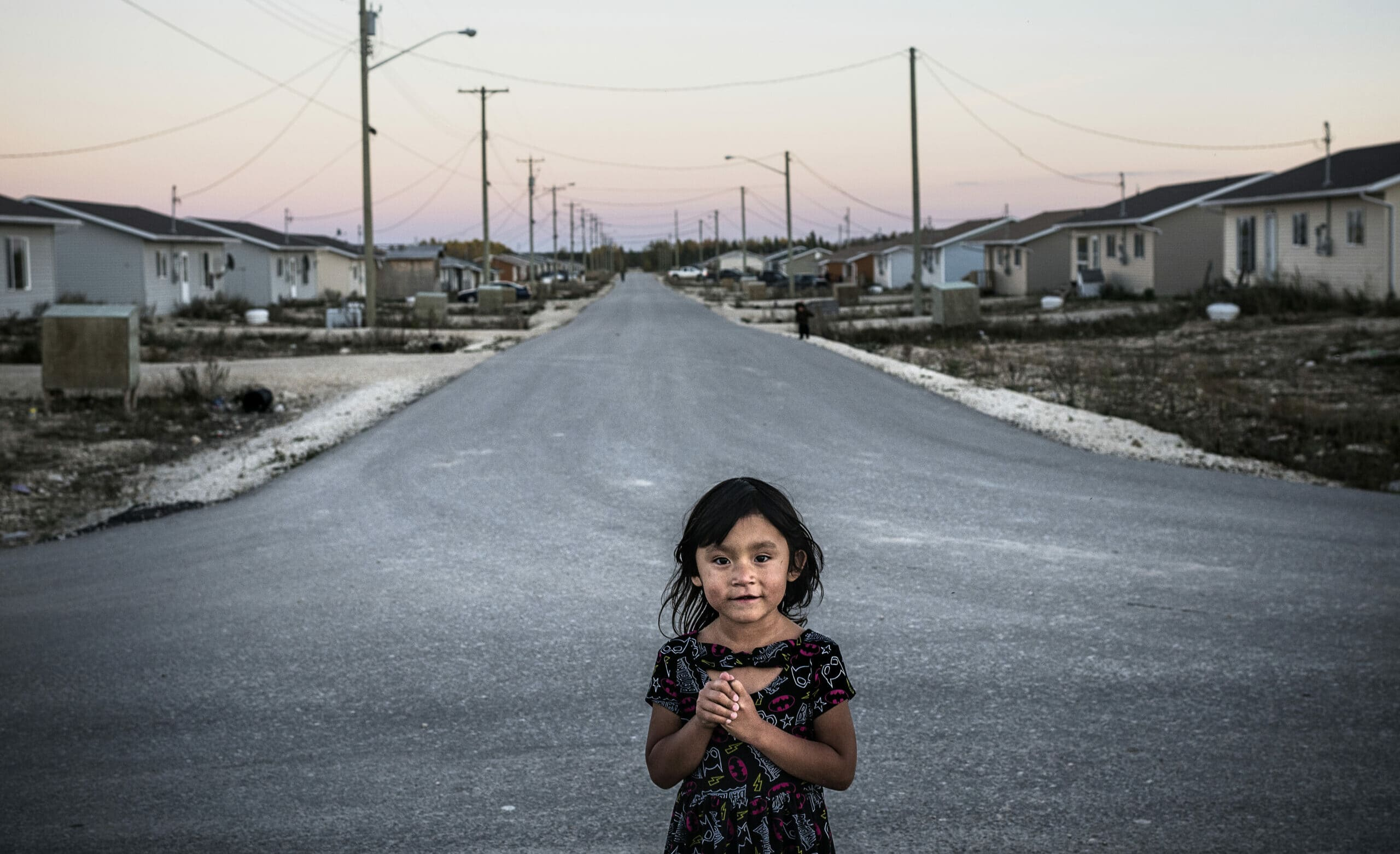 young girl on empty residential street in Easterville, Manitoba.