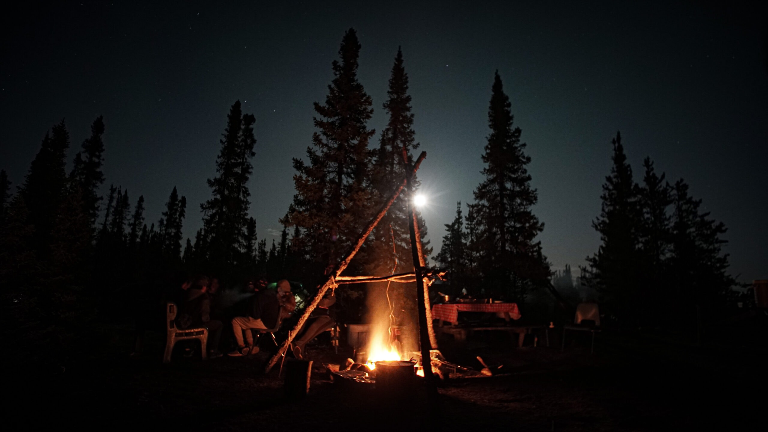 campfire at night with people sitting around it