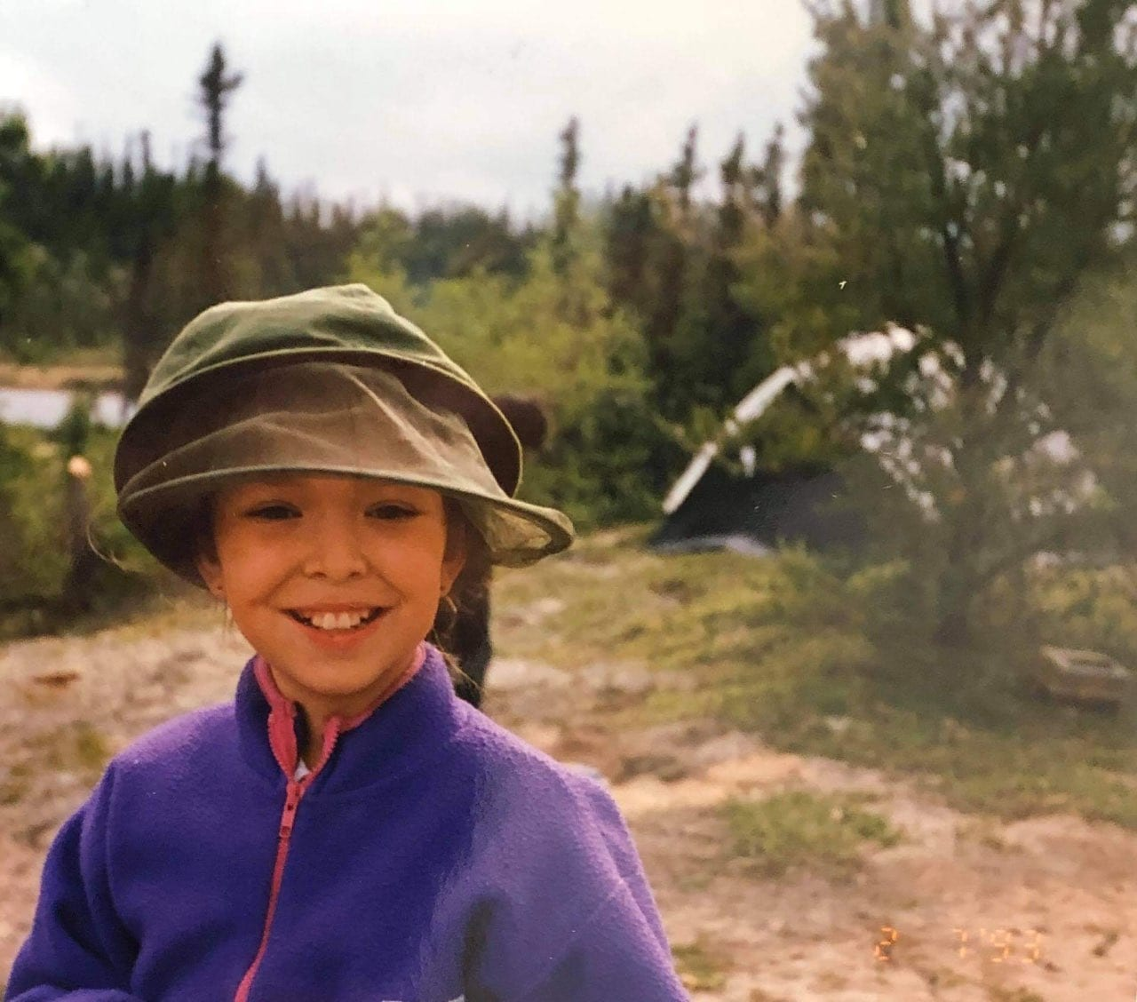 Young Stephanie Thorassie standing outside near a campsite