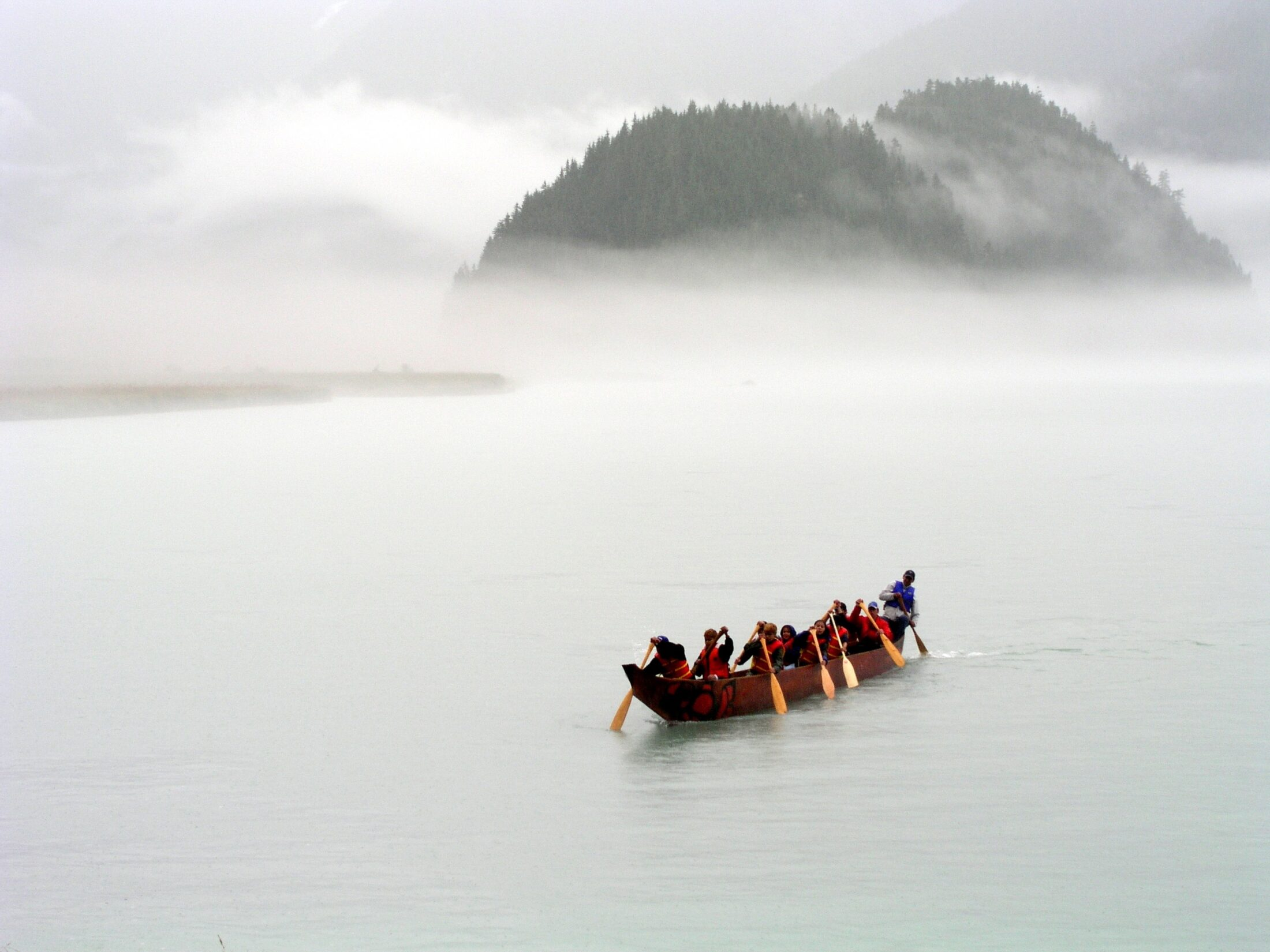 Haisla youth paddle a canoe at Misk'usa. Fog surrounds them