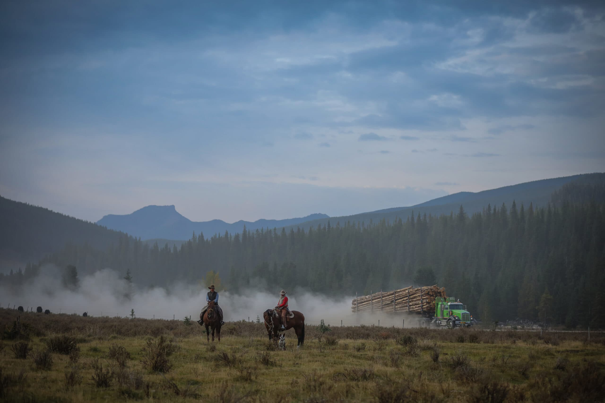 John Smith and Laura Laing ride on horses while log truck passes in the background