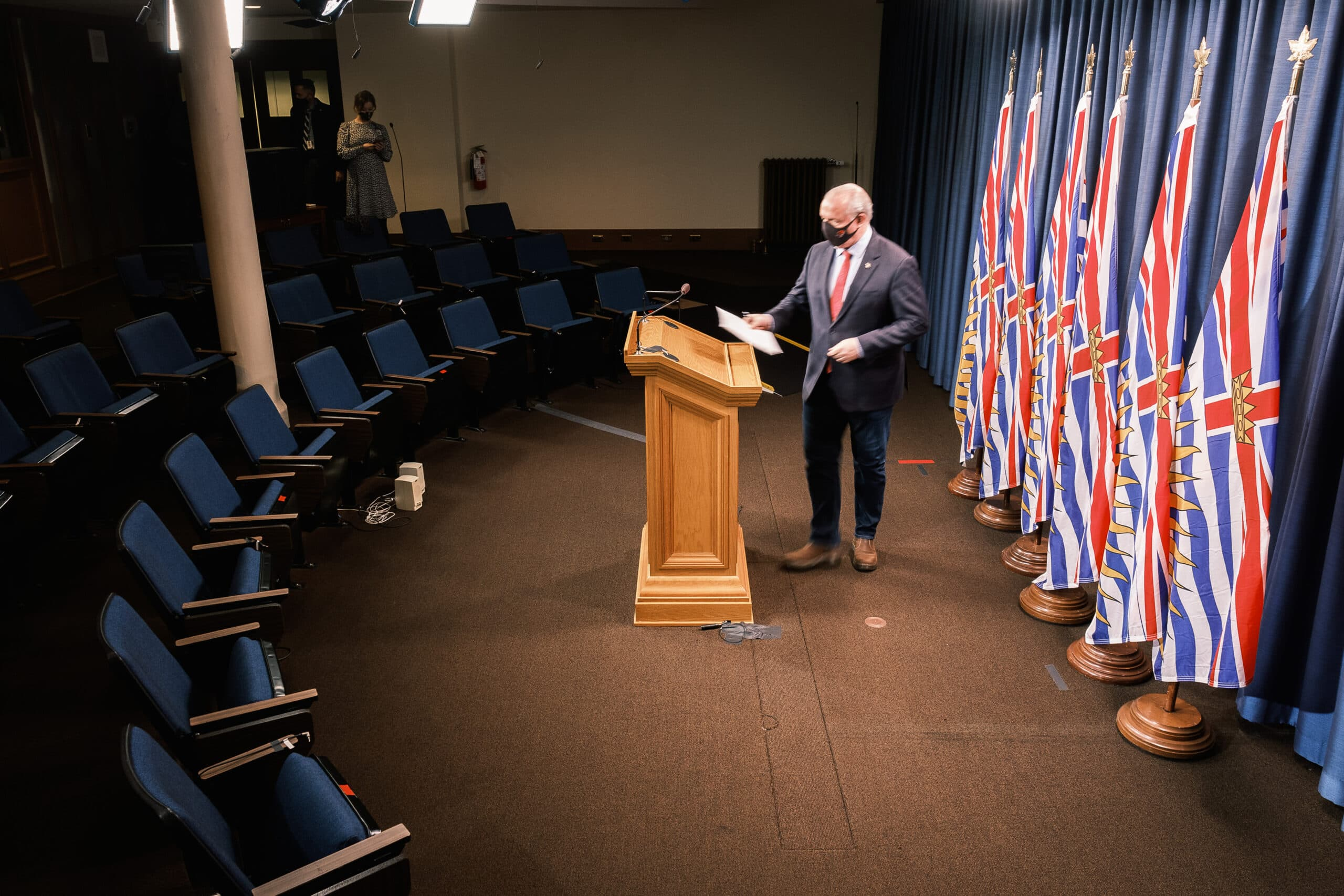 John Horgan standing at podium by himself with a mask on