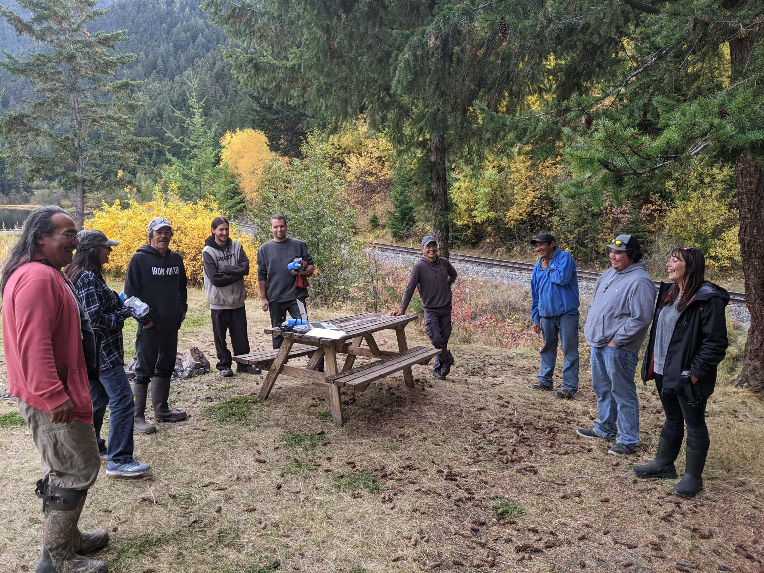 group of people stand around picnic table in forest