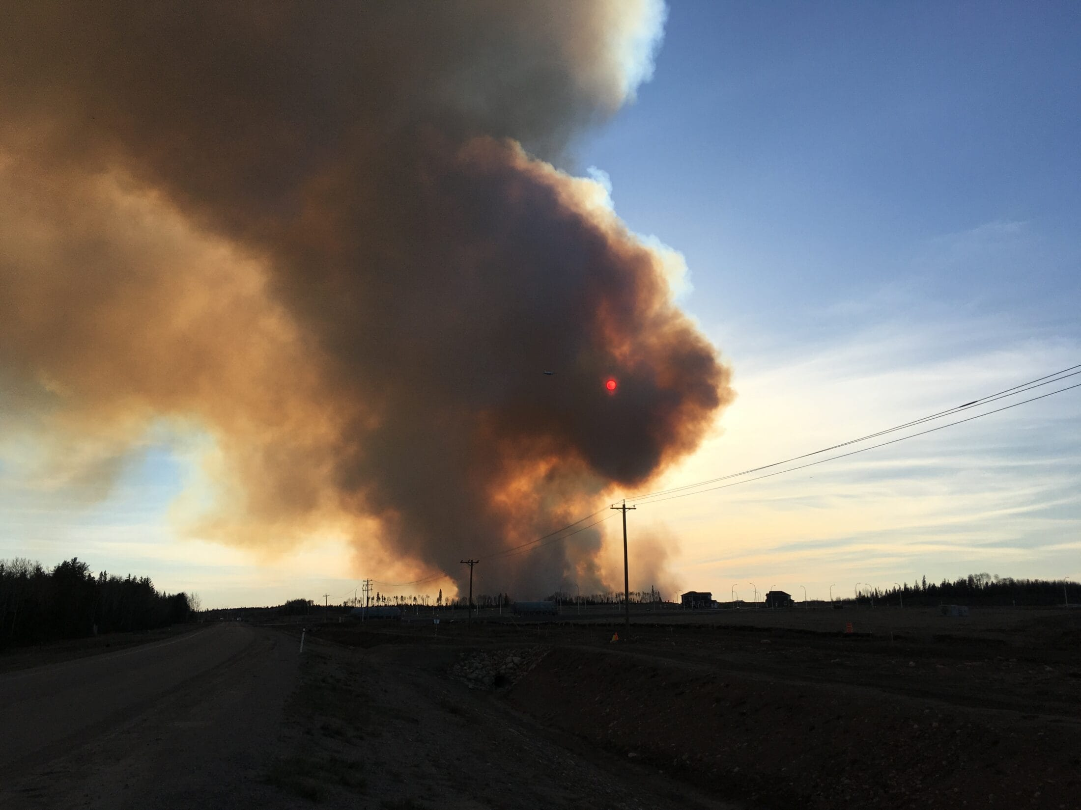 huge smoke cloud. photo taken from a road next to a field