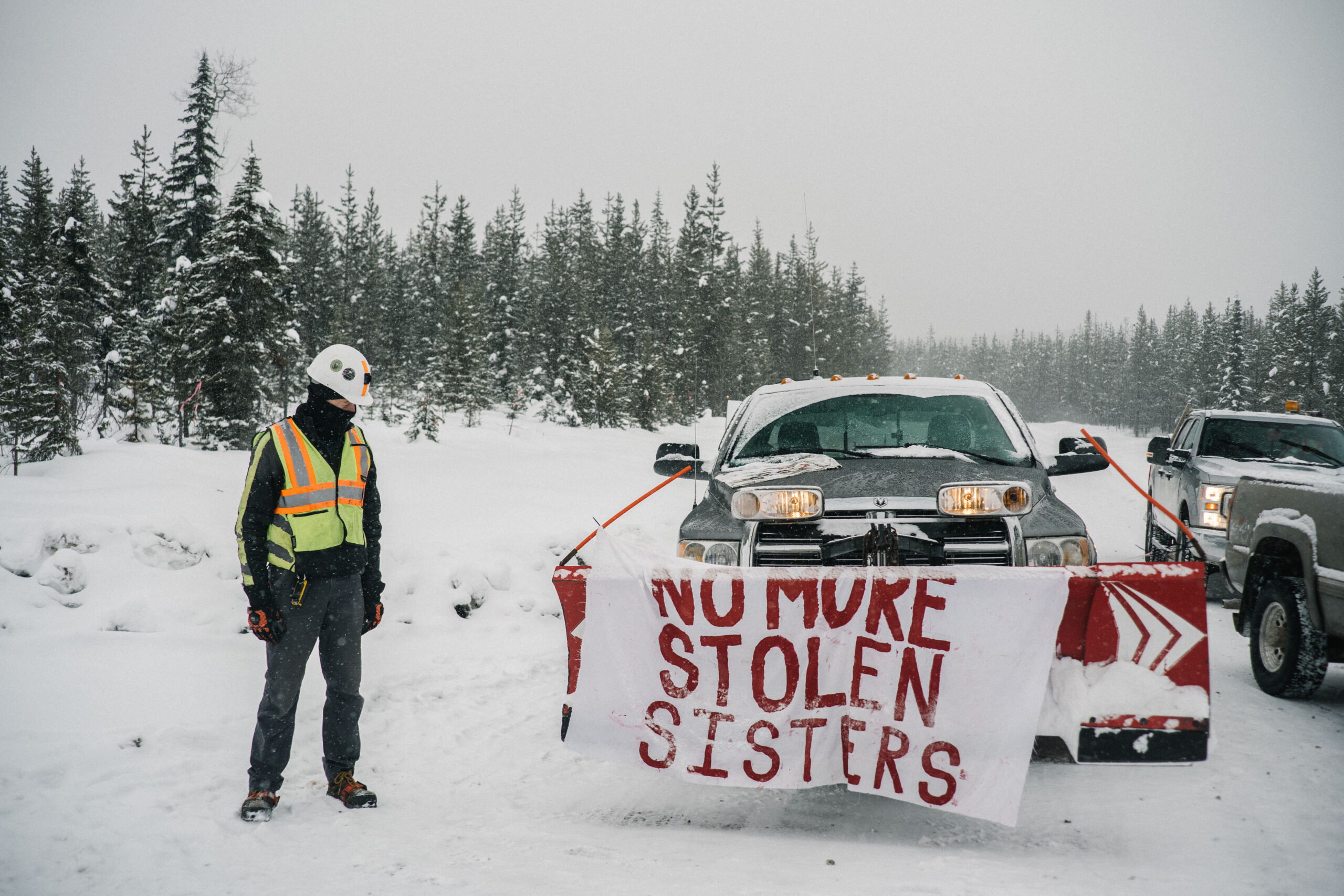 """A Coastal GasLink worker looks at a sign that says """"no more stolen sisters"""" hung on a truck"""