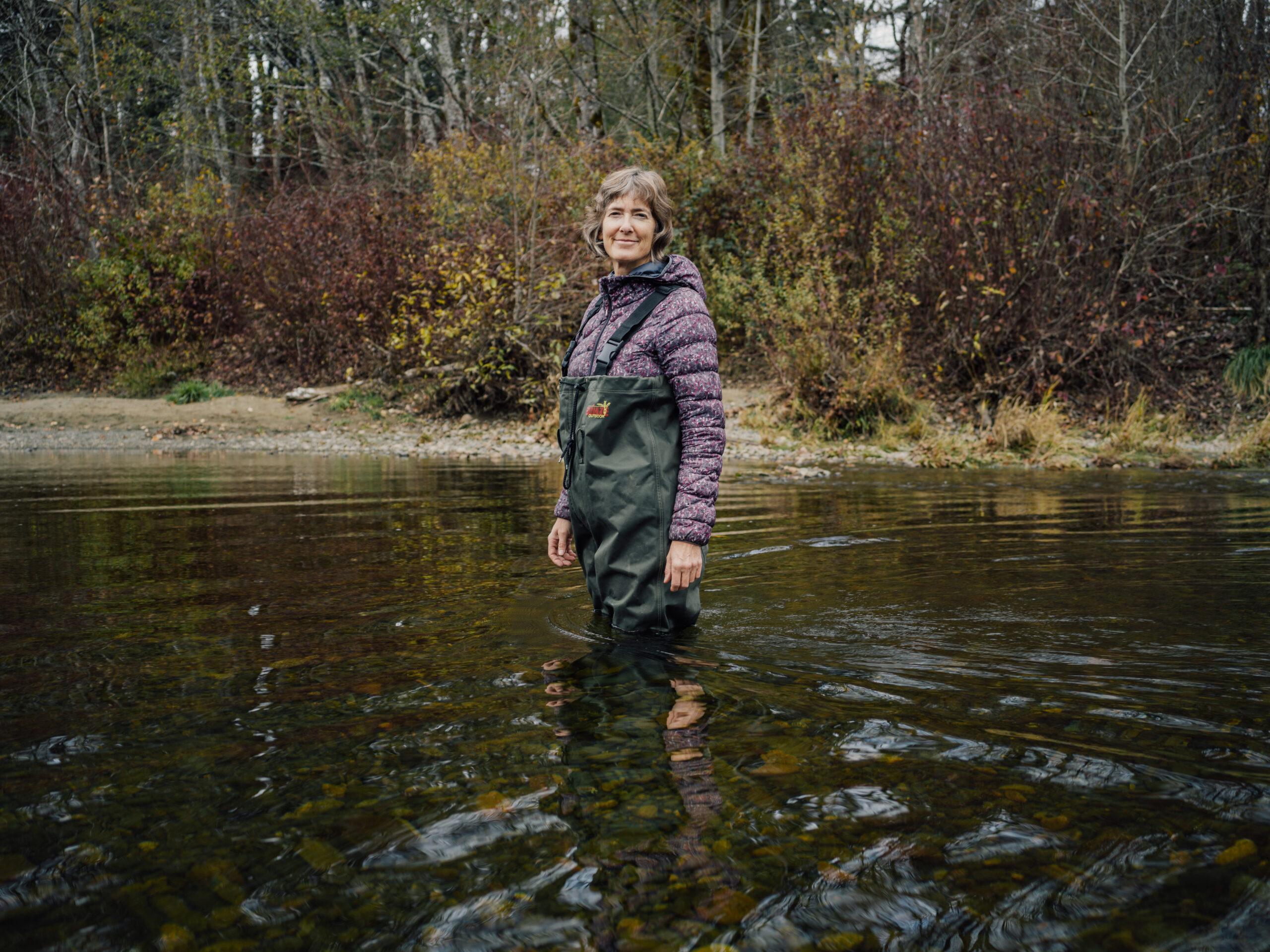 Caroline Hiem stands in hip waders in river