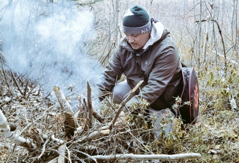 Shane Bird prepares a fire outdoors