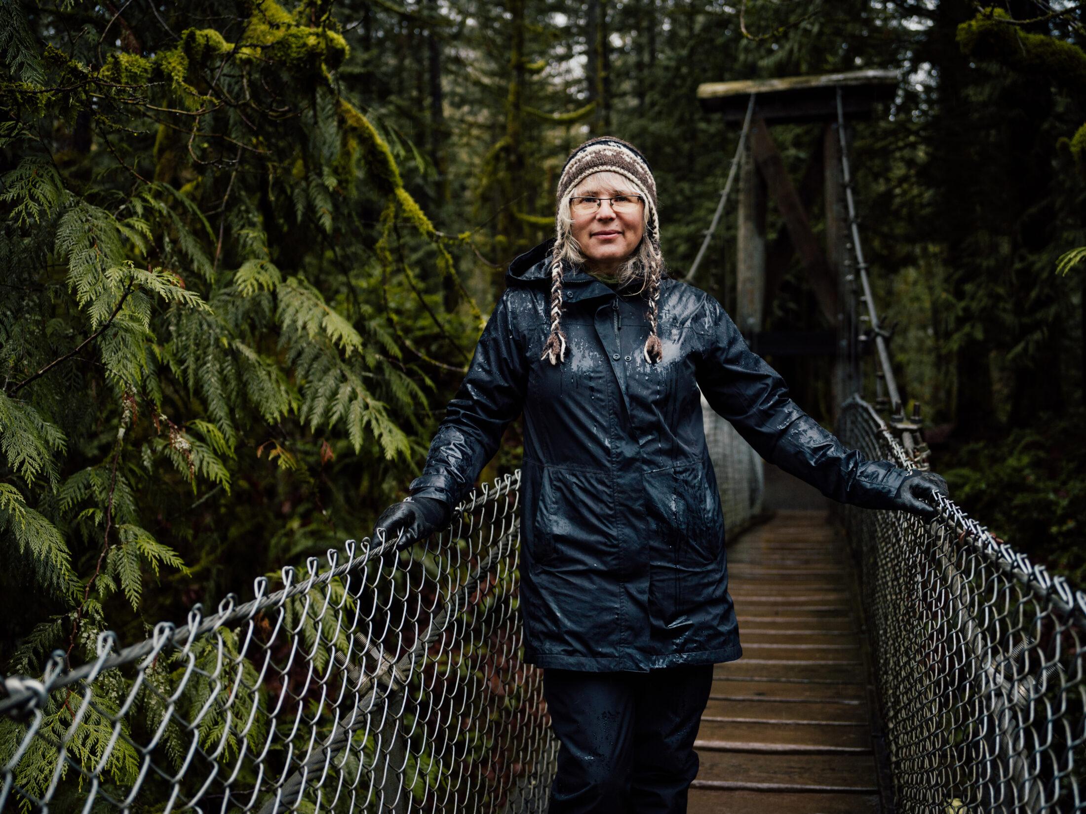 Cheri Ayers stands on a suspension bridge