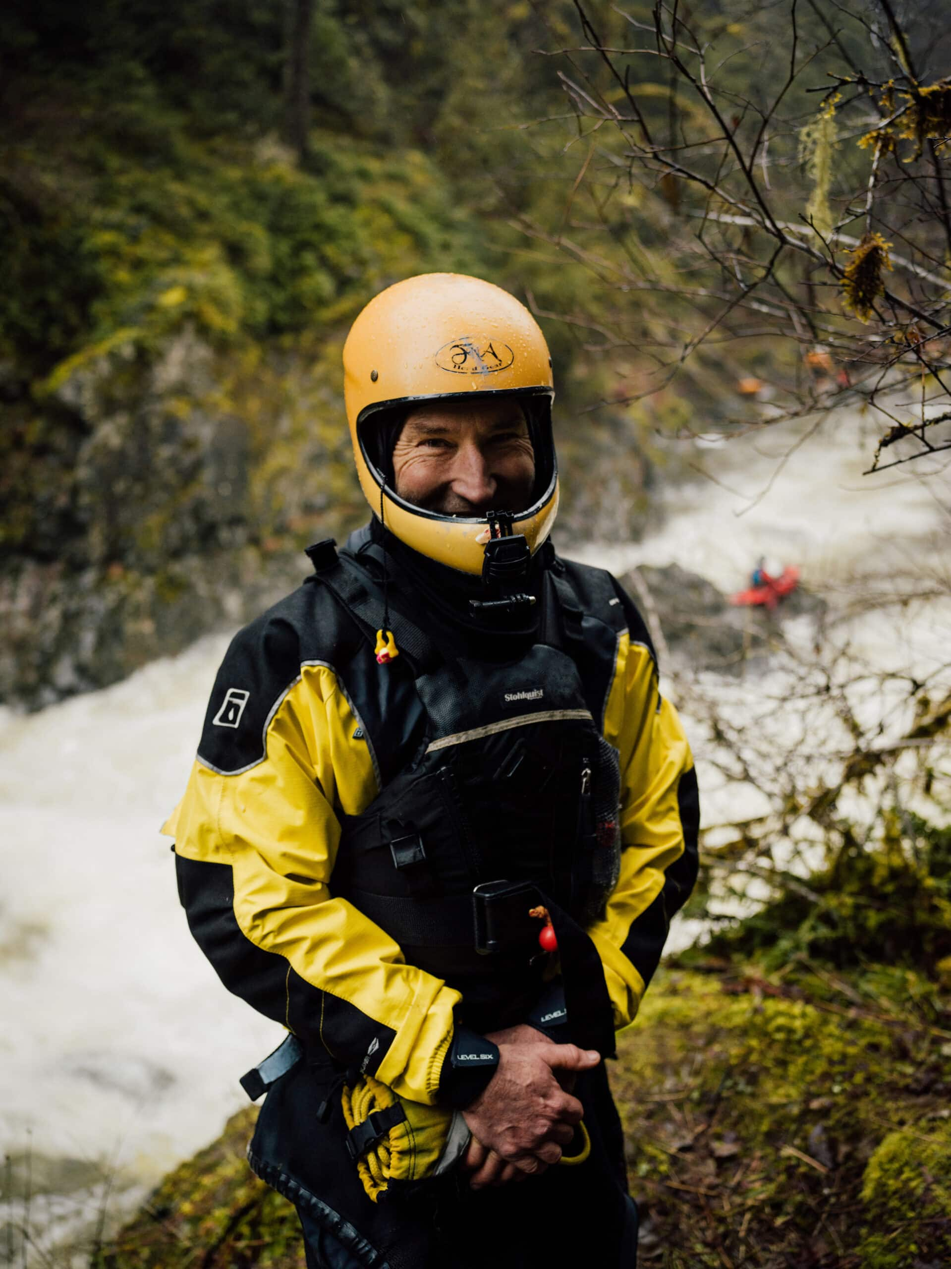 Stephen Hunt, white water kayaker stands by the Koksilah River in a yellow helmet