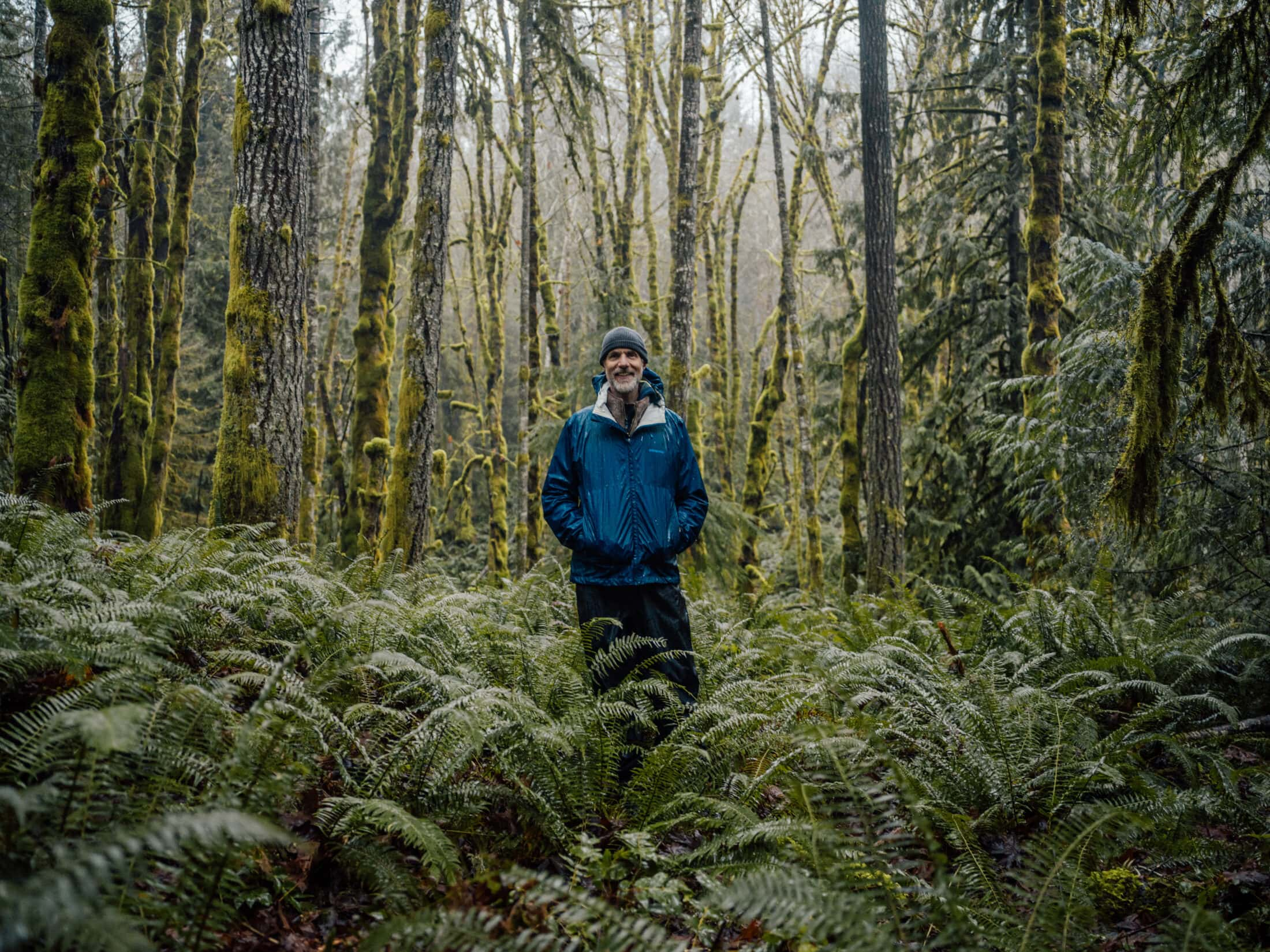 Tom Rutherford stands in a lush green forest