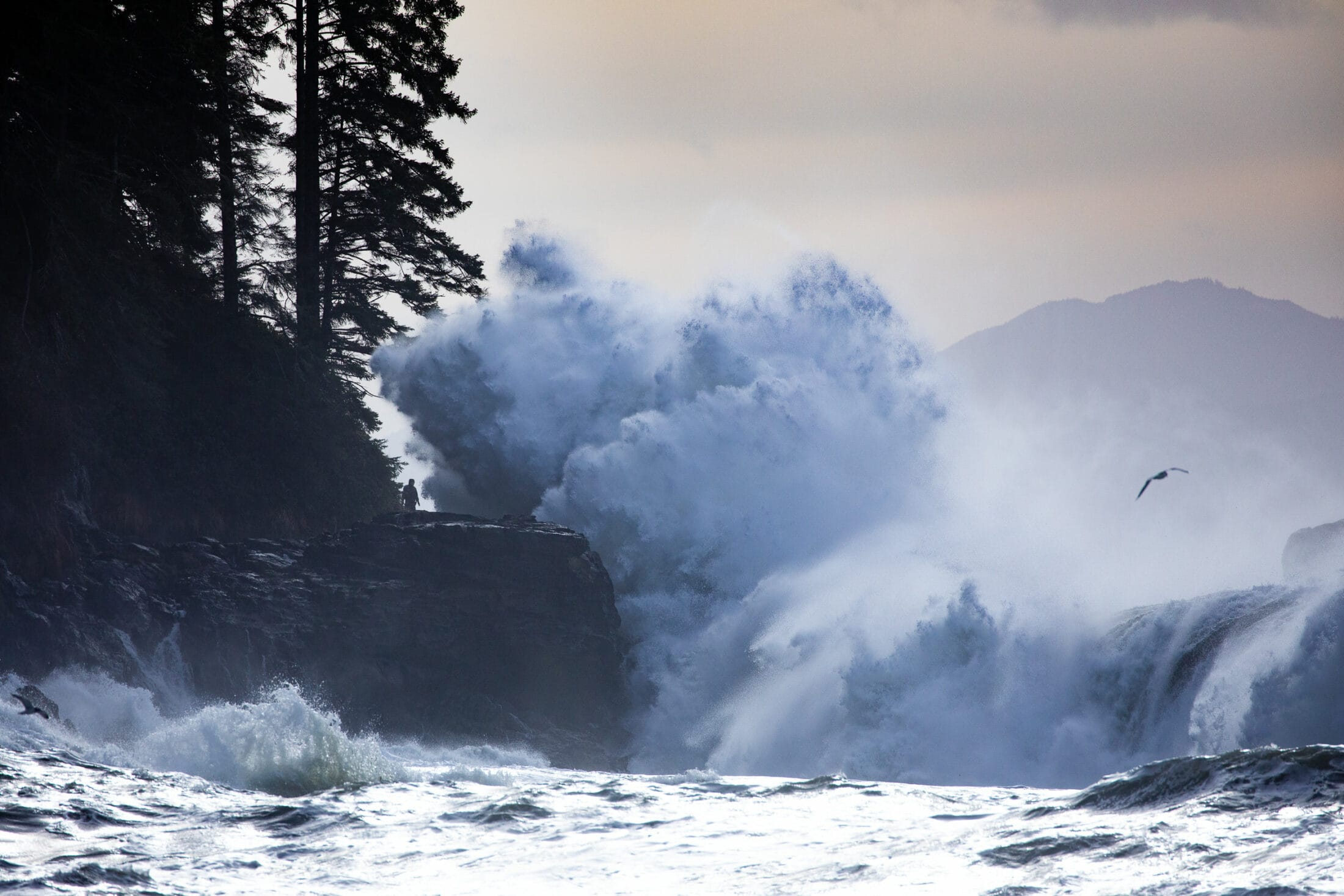 Enormous waves crash against the rocks on the shore of Sombrio Beach