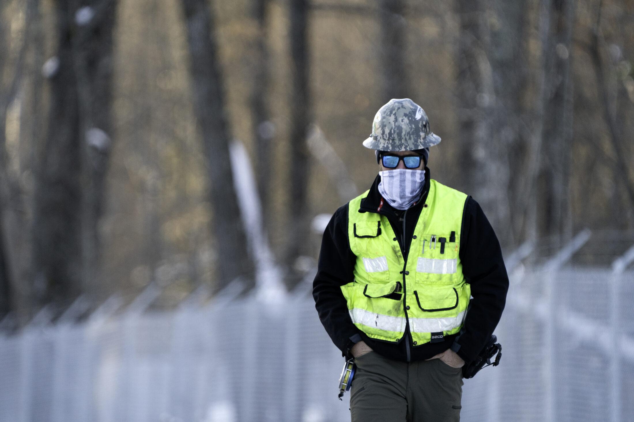 enbridge worker walking outside wearing a mask