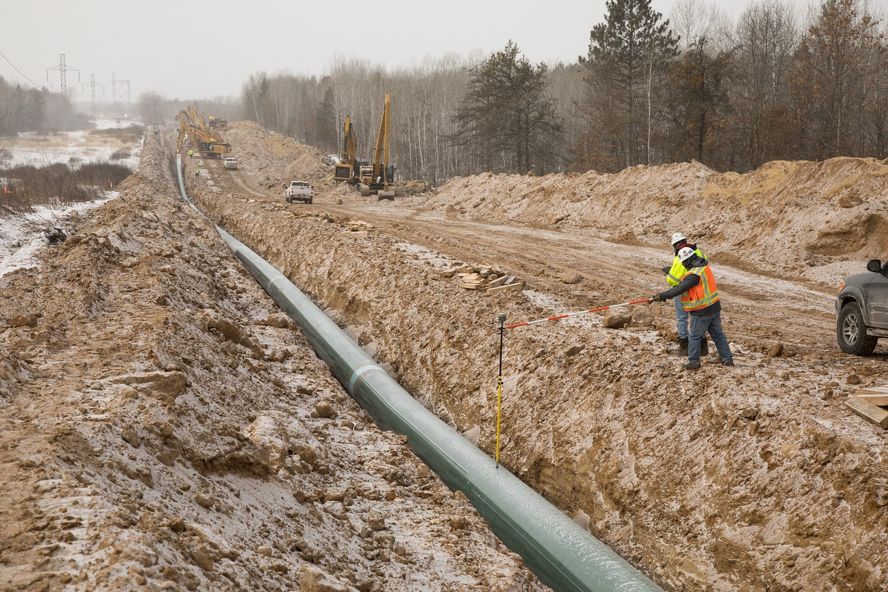 overturned earth with a pipeline running through and construction workers standing around