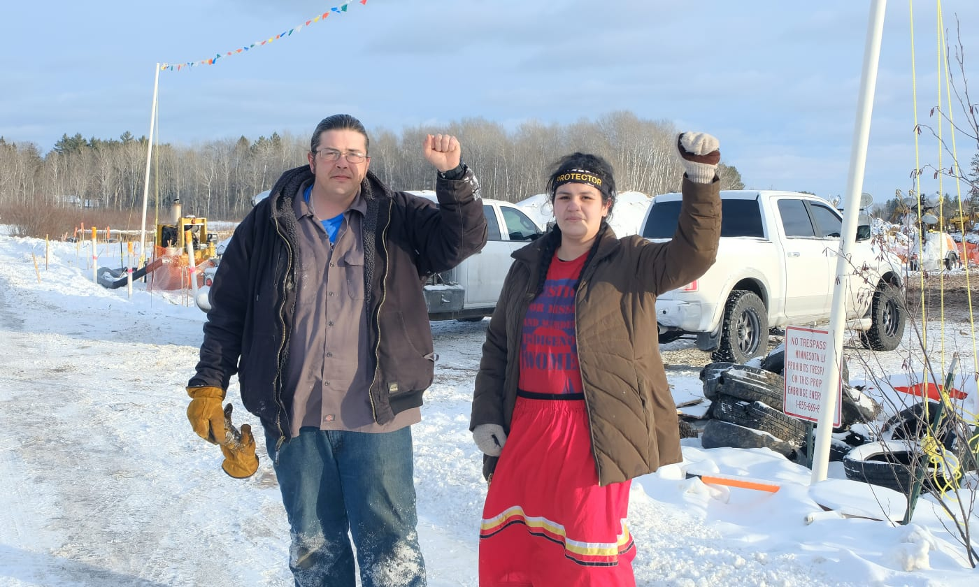 Jason Goward and Taysha Martineau standing outside with their left fists raised
