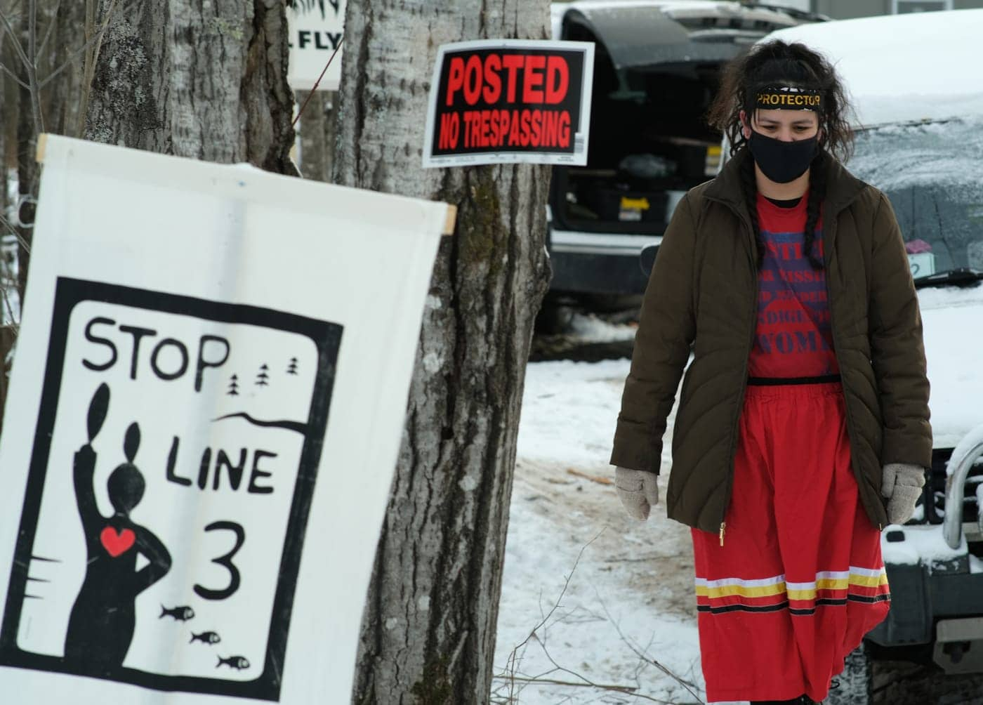 """Taysha Martineau walking down a snowy street with a """"stop line 3"""" sign in the foreground"""