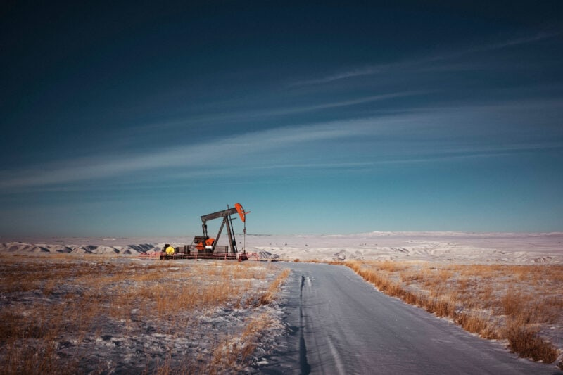 An oil and gas pumpjack beside an empty road