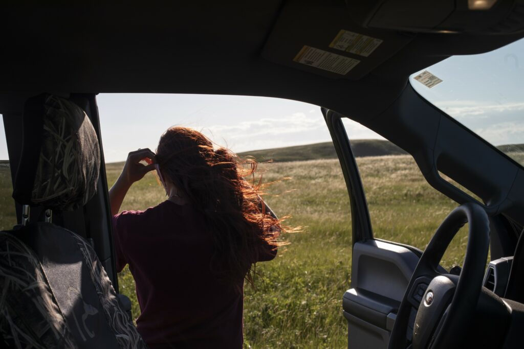 Mickenzie Plemel-Stronks looks out onto grassland from a car