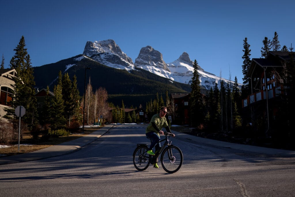 person biking on a road with The Three Sisters peaks in the background