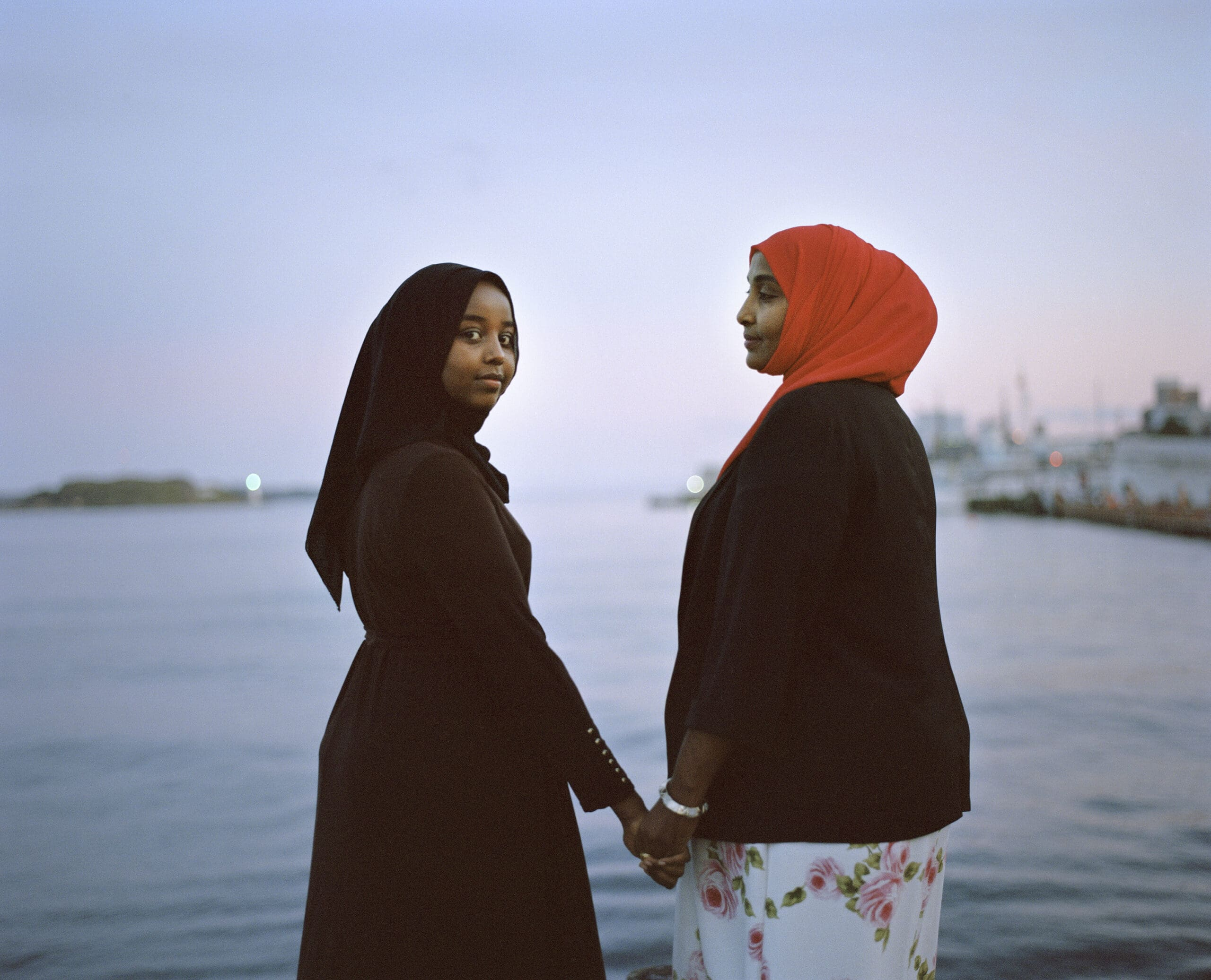 Two Muslim women holding hands posing by water