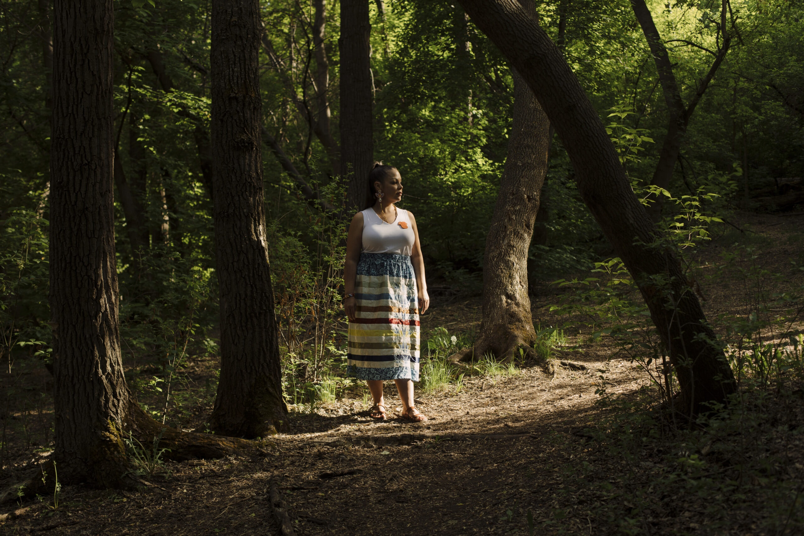 Crystal Lameman standing in a forest