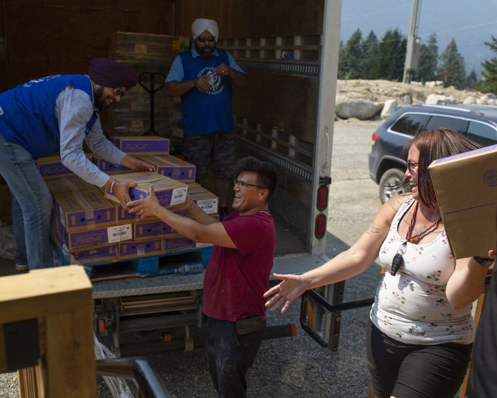 volunteers handing out food and water from a truck