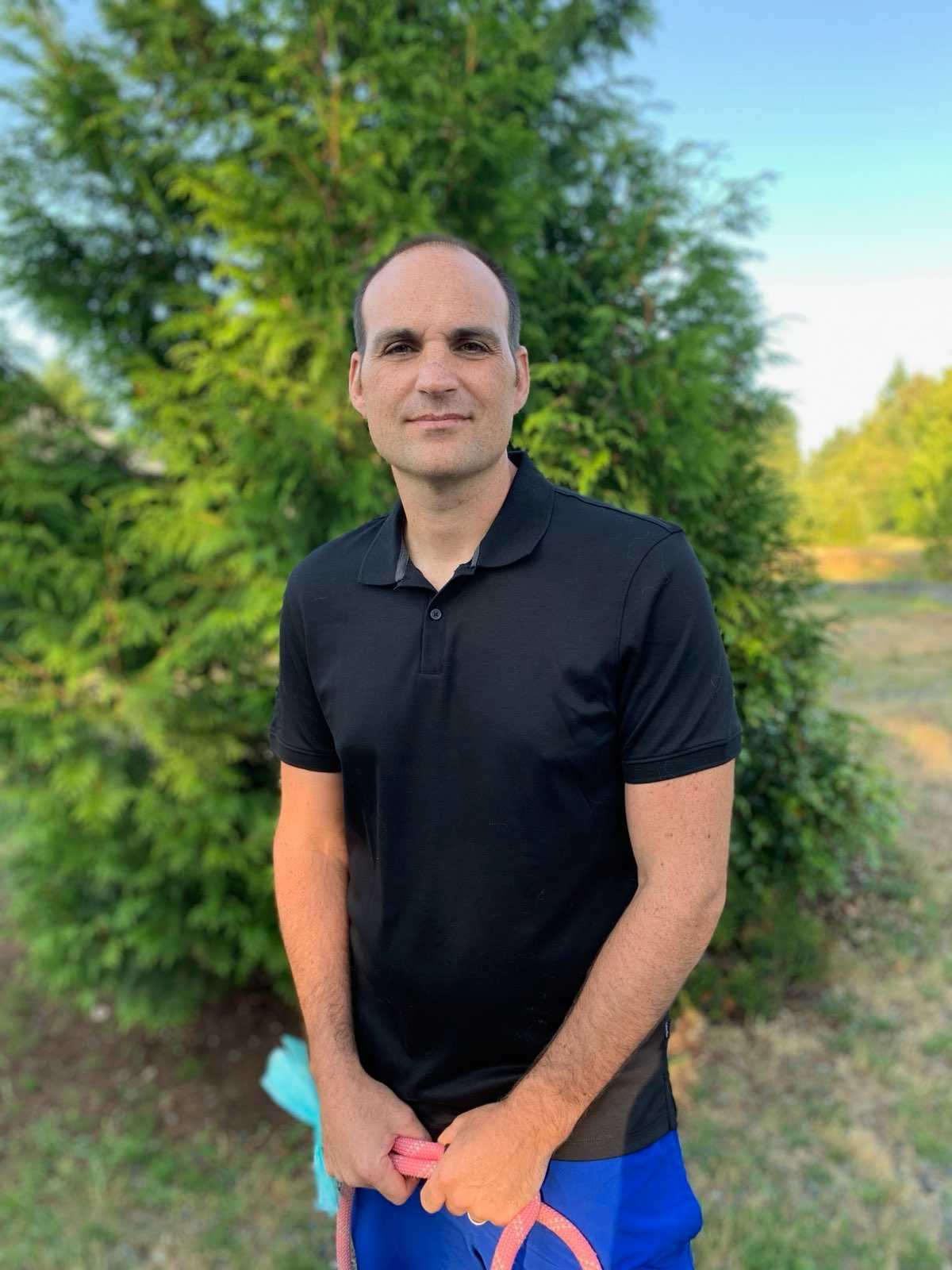 a man in a black polo shirt standing in front of a tree