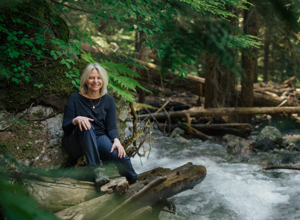 suzanne simard sitting in a forest