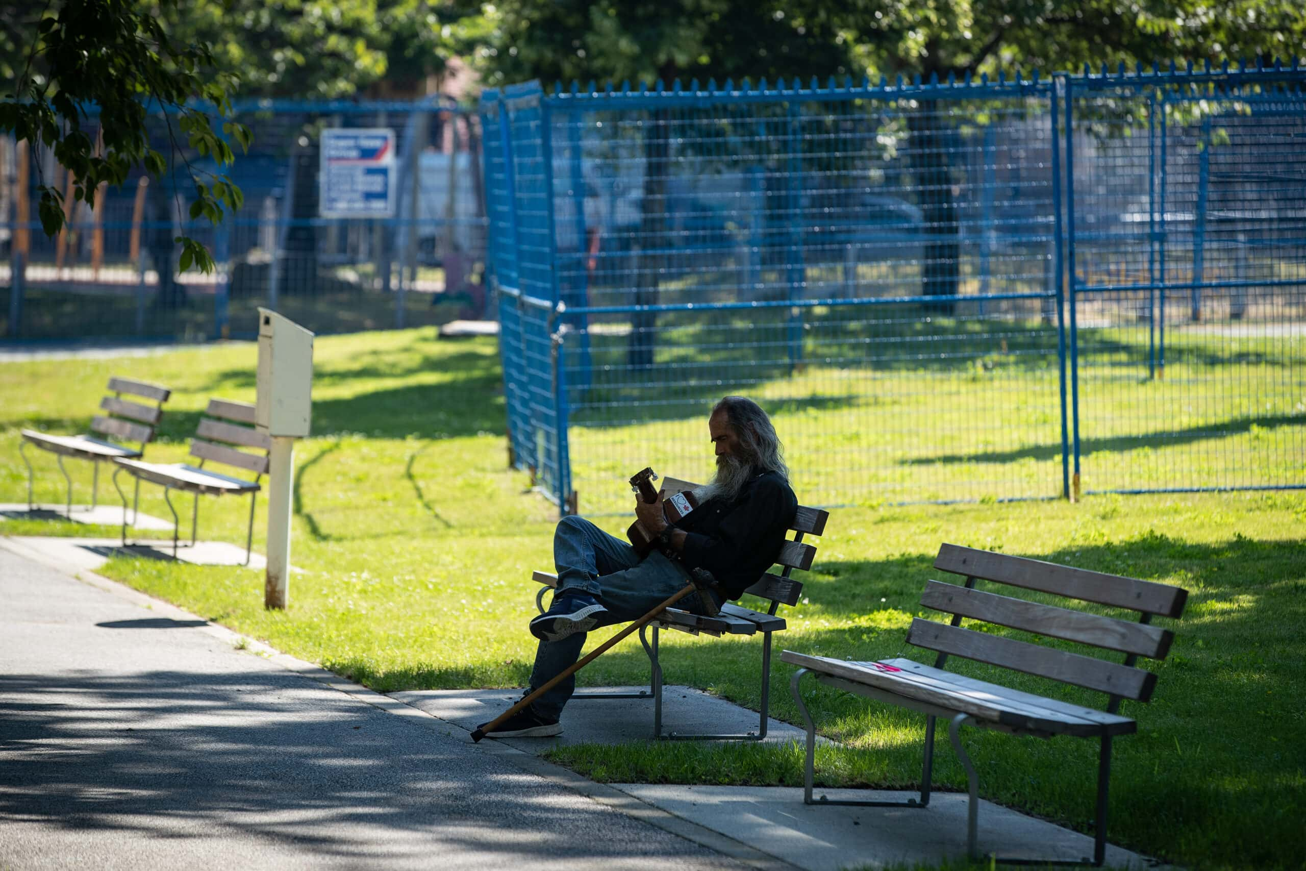 a man sitting on a bench plays guitar