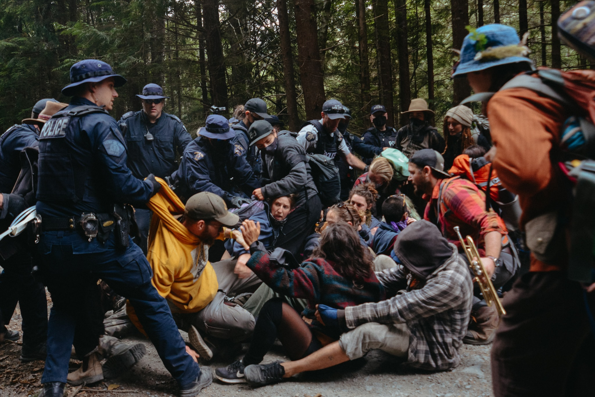 RCMP surrounding a group of protestors on the ground at Fairy Creek