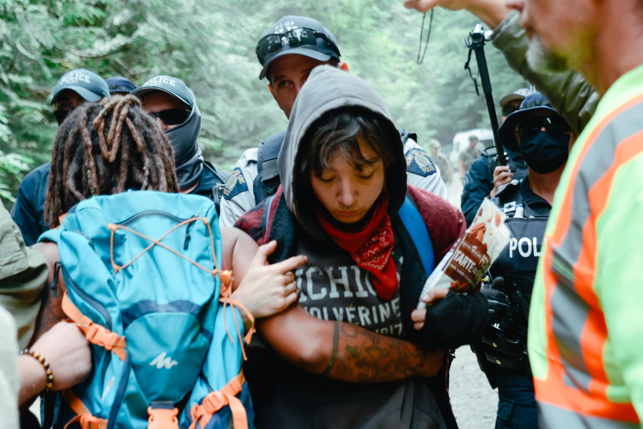 RCMP surrounding a protestor at Fairy Creek blockades
