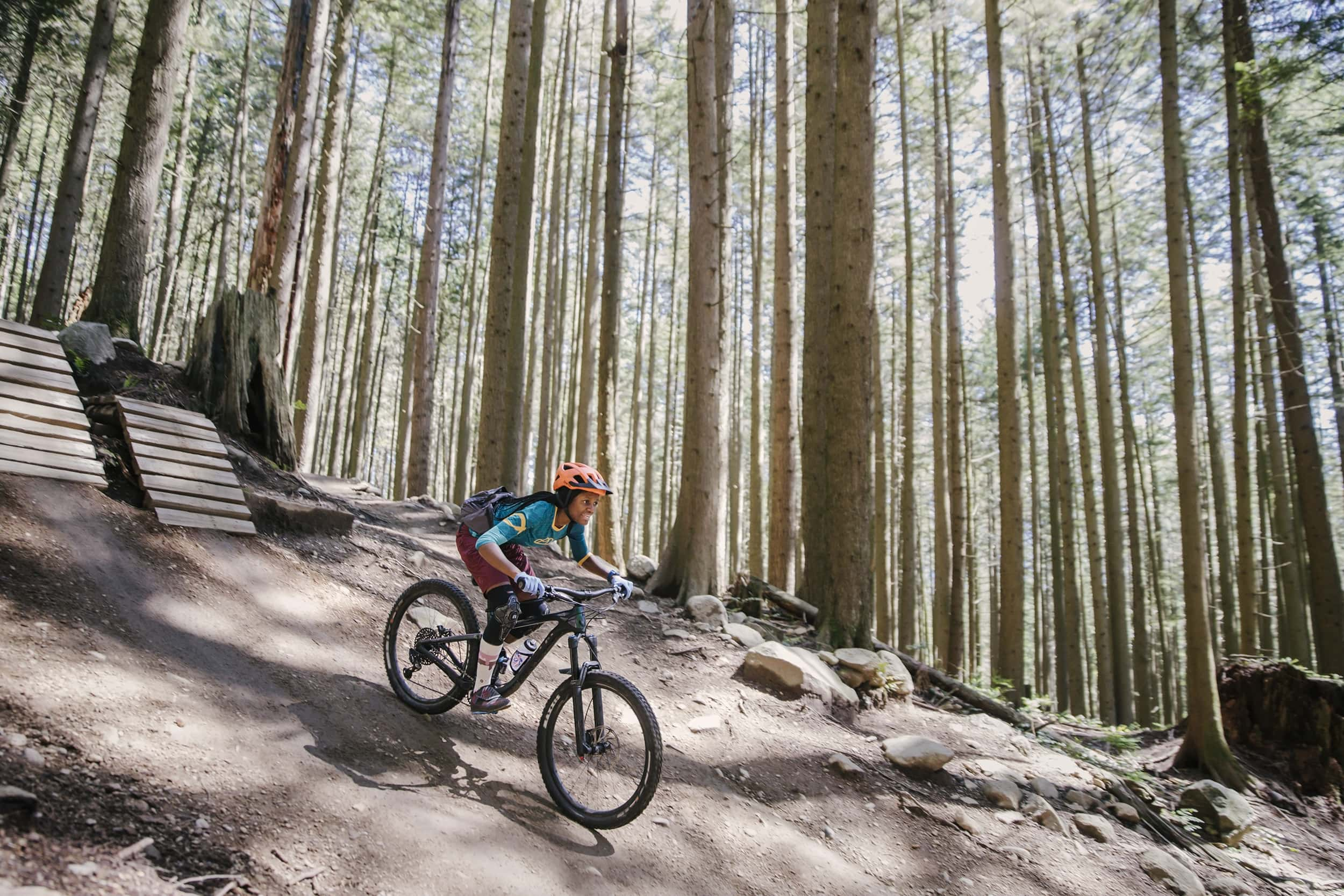 Judith Kasiama (she/her) rides her mountain bike along a trail in Mount Fromme