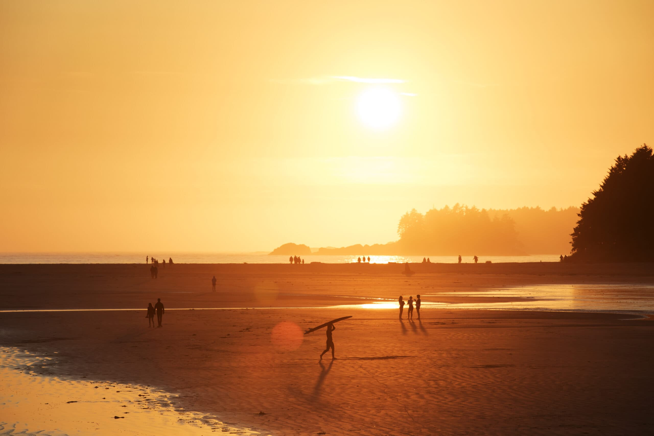 A surfer walks out of the ocean at sunset on Chesterman Beach