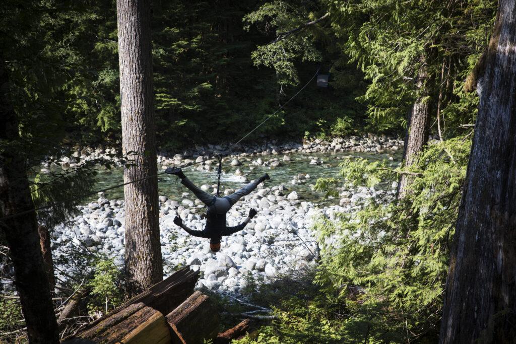 WestCoast WILD Zipline guide Luke Thomas suspends from a zipline