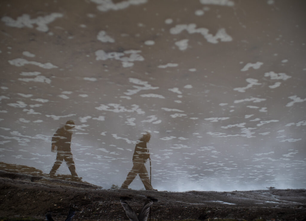 the image of two men are reflected in muddy water