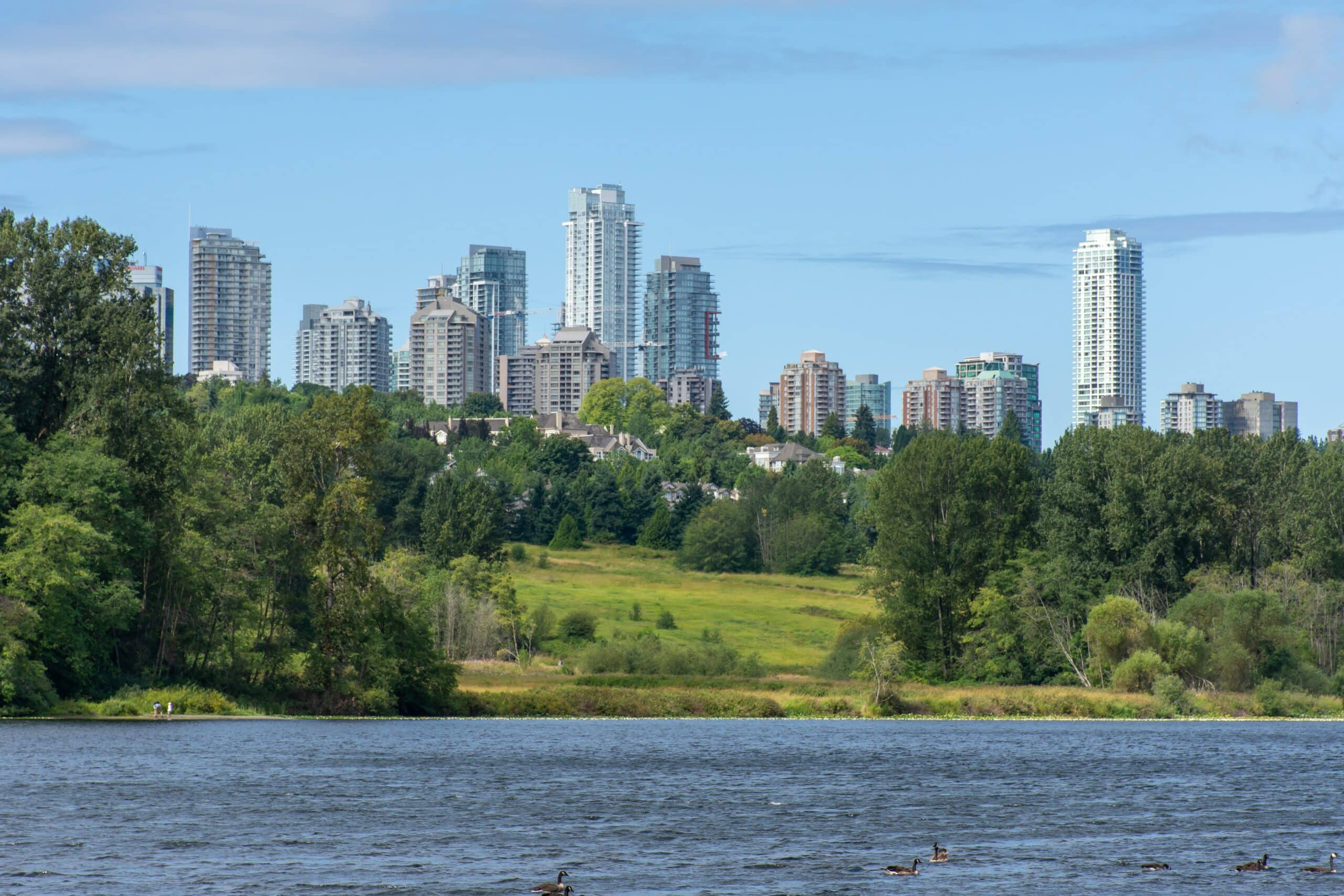 Panorama of Burnaby, British Columbia, Canada skyline from Deer Lake looking towards Metrotown and apartment complexes on a sunny summer day.