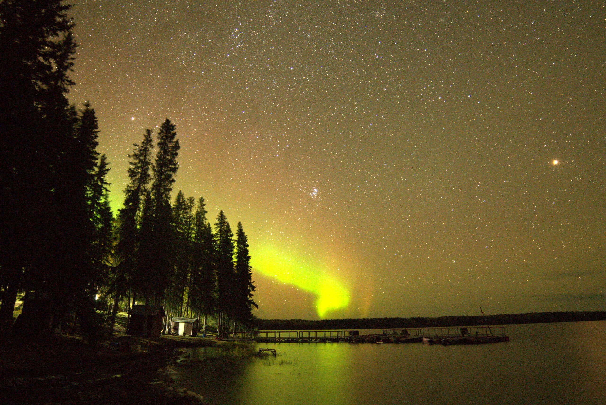 northern lights by a lake